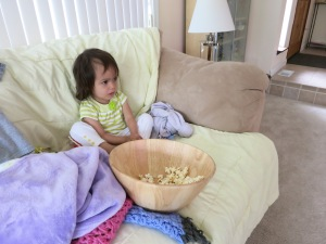 "Big girl eating popcorn and watching ""The Very Hungry Caterpillar."""