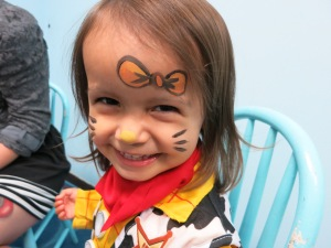 Getting her face painted at a preschool Halloween party.