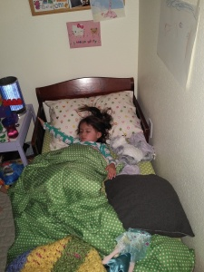 Sleeping in her toddler bed